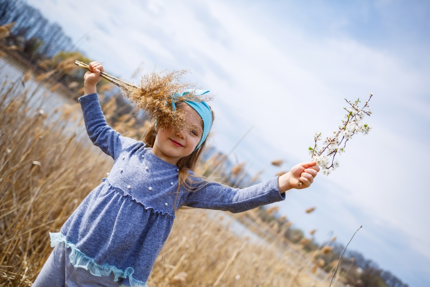 little girl child holds dry reeds and a branch with small white flowers in hands, sunny spring weather, smilling and joy of the child